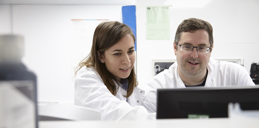 Two researchers discussing experiment results on a computer screen.